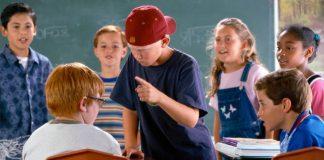 Imagem de três crianças intimidando um menino na escola