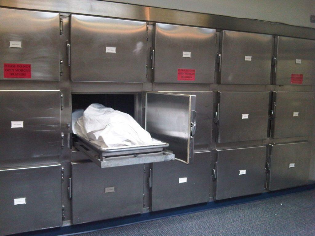 Imagem de um necrotério com uma das gavetas puxadas. O corpo está coberto.