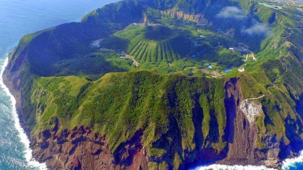 Imagem aérea da lha de Aogashima, onde se vê um vulcão dentro de uma cratera maior. Ambos rodeados por estradas.